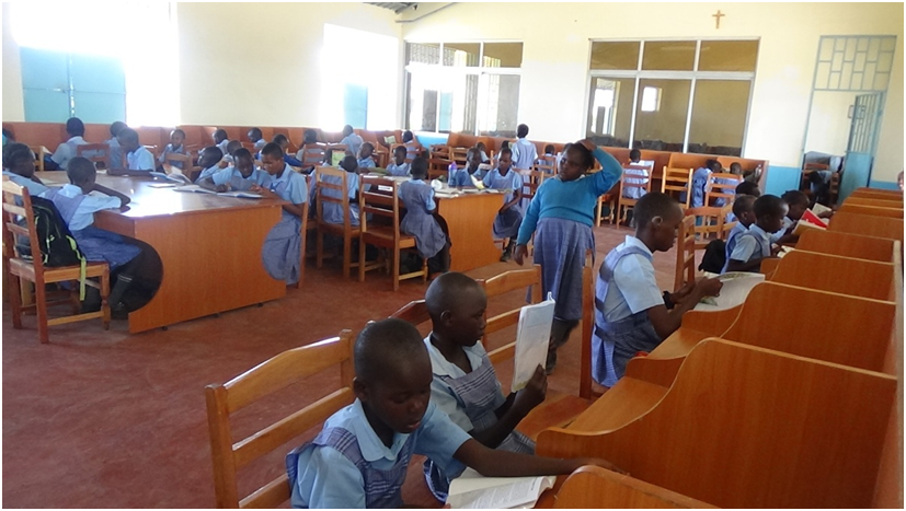 Pupils in the Library.  We have a few books bought by the school and others through donations. We still require more books therefore call upon well wishers to help us equip the library.